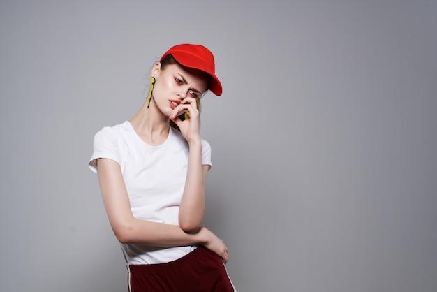 Гламурная женщина в красной шапочке летняя мода украшение позирует светлом фоне. фото высокого качества