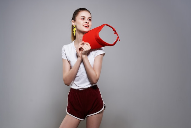 明るい背景のポーズの赤い帽子の夏のファッション装飾の魅力的な女性