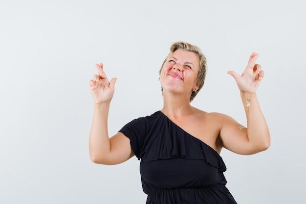 Donna affascinante tenendo le dita incrociate in camicetta nera e guardando concentrato