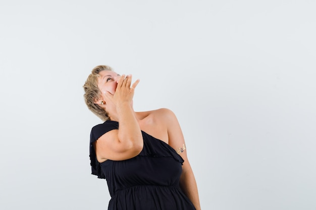 Гламурная женщина смеется, глядя вверх в черной блузке и выглядит весело. передний план. место для текста