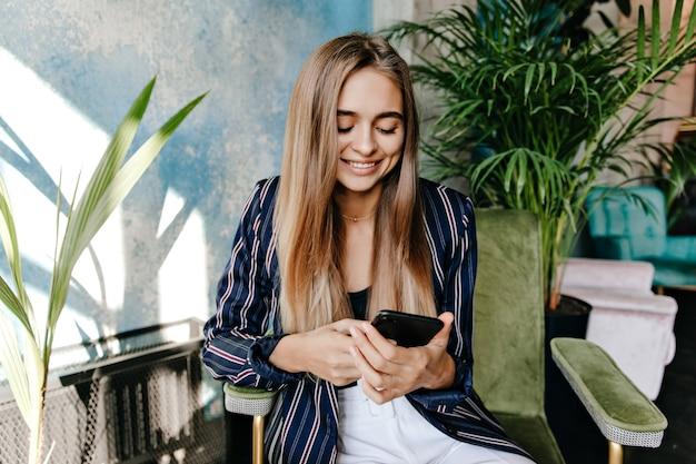 사무실에 앉아있는 동안 전화 화면을보고 매력적인 여자. 팔의 자에서 쉬고 놀라운 예쁜 여자의 실내 샷.