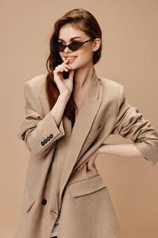 안경을 쓴 매력적인 여성 모델이 손으로 얼굴을 만지고 옆을 쳐다본다