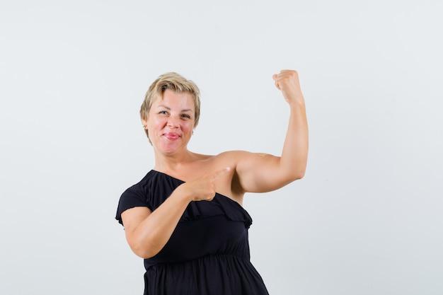 黒のブラウスで腕の筋肉を指差して満足そうなグラマラスな女性。正面図。