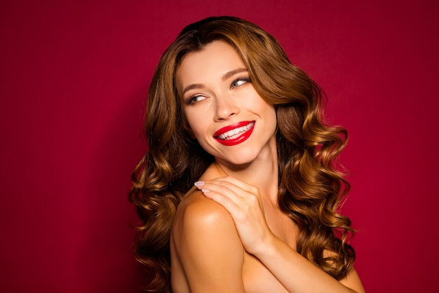 Glamorous woman posing against the red wall