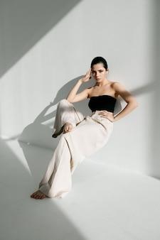 Гламурная женщина позирует возле белой стены в помещении. фото высокого качества