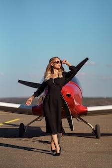 飛行機でポーズをとる華やかな女性
