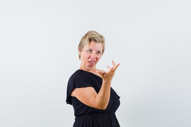 黒のブラウスで質問マナーで手を上げて好奇心旺盛なグラマラスな女性