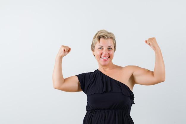 Donna affascinante che mostra il potere del suo braccio in camicetta nera e sembra allegra. vista frontale.