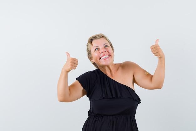 Гламурная женщина показывает палец вверх в черной блузке и выглядит радостной