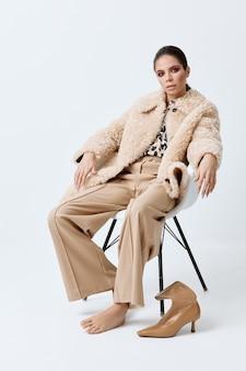 白い毛皮のコートのファッショナブルな服のポーズで椅子に座っている魅力的な女性。高品質の写真