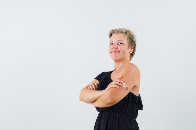 Гламурная женщина, стоящая со скрещенными руками в черной блузке и выглядящая уверенно