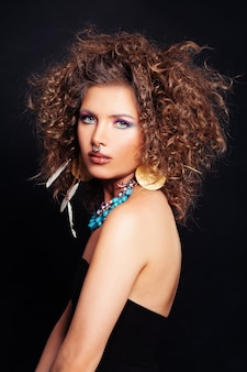 Glamorous woman wit curly hairstyle makeup and accessories in the ethnic style