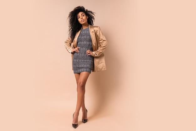 ベージュの壁にポーズをとるモダンな光沢のあるドレスと金色のシルクのジャケットの巻き毛の魅力的な女性。パーティー気分。
