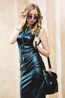 黒のスタイリッシュなドレスに身を包んだ眼鏡をかけた華やかな女性