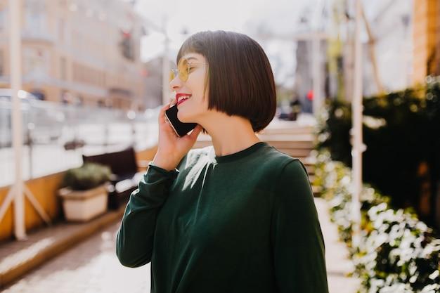 電話で話している短い散髪の魅力的な女性。通りで誰かを呼び出す緑のセーターの美しいブルネットの少女。
