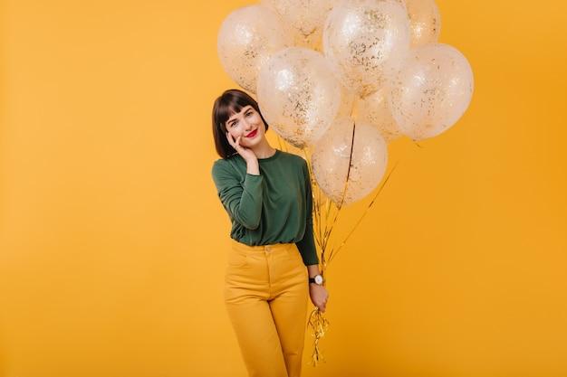 きらめく風船の束でポーズをとるストレートヘアの華やかな女性。緑のセーターと黄色のズボンでのんきな女の子の笑顔の屋内ショット。
