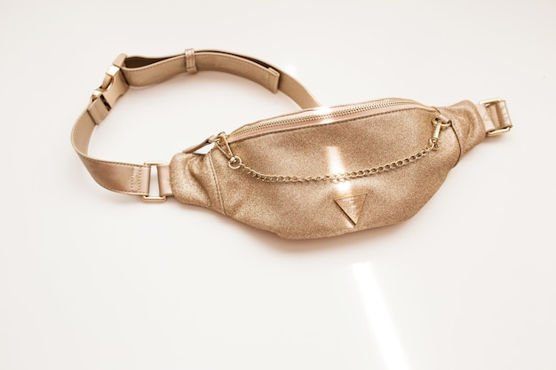 Glamorous women's belt bag of golden color on a white isolated background. fashion handbag with a gold chain. close-up.
