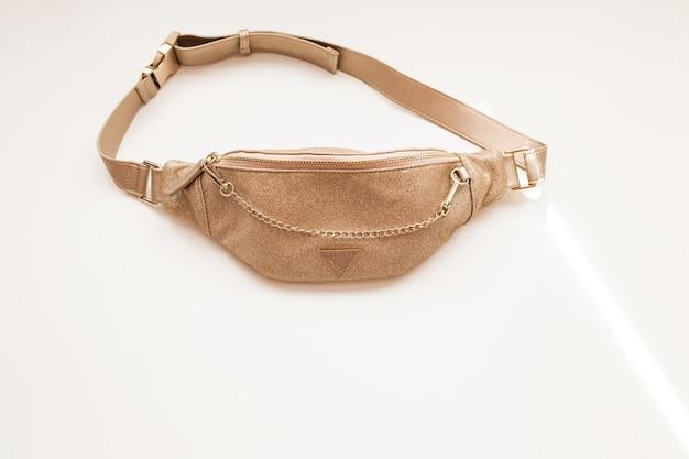 白い孤立した背景に金色の華やかな女性のベルトバッグ。ゴールドチェーンのファッションハンドバッグ。閉じる。