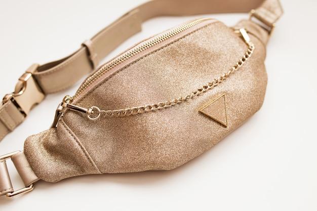 격리 된 흰색 배경에 황금 색상의 매력적인 여성 벨트 가방. 골드 체인 패션 핸드백.