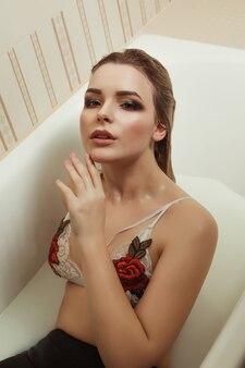 刺繡のレースのランジェリーの魅力的な若いモデルは、ミルクでお風呂に入ります