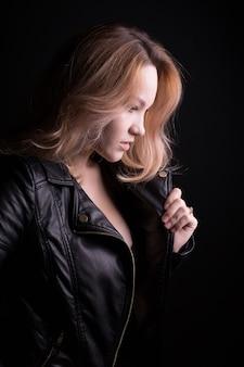 緑豊かなウェーブのかかった髪の魅力的な若いモデルは、黒い背景にポーズをとって、革のジャケットを着ています
