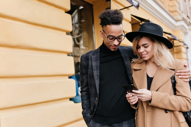 Glamorous young woman in beige coat telling someone to african man. pleased black guy looking at phone which holding beautiful blonde girl.