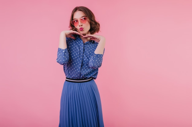 Glamorous young woman in blue blouse funny posing  indoor photo of adorable short-haired girl in pink sunglasses.