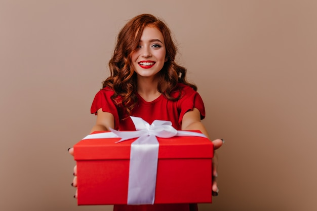 Glamorous young woman holding christmas gift. wonderful curly female model preparing for new year party.