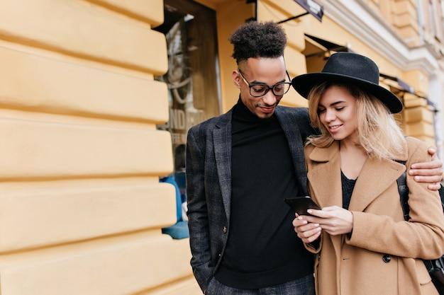 アフリカ人男性に誰かを告げるベージュのコートを着た魅力的な若い女性。美しいブロンドの女の子を抱いている電話を見て喜んでいる黒人の男。