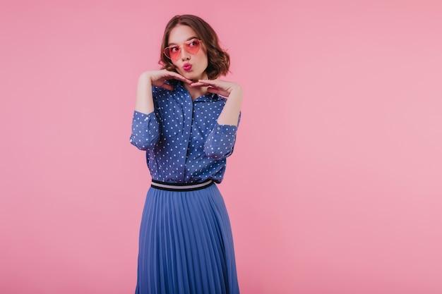 青いブラウスの魅力的な若い女性面白いポーズピンクのサングラスで愛らしい短い髪の少女の屋内写真。