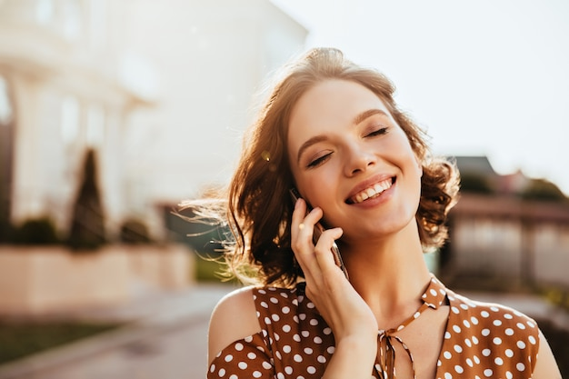 目を閉じて電話で話している魅力的な若い女性。短い茶色の髪のかわいい白人の女の子の屋外ショット。