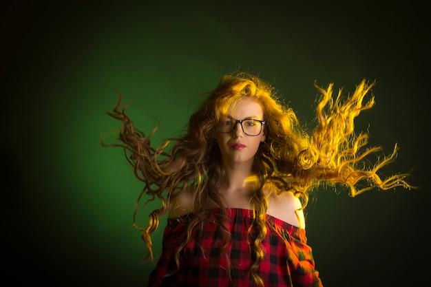 動きのある髪のメガネをかけている魅力的な若い女性