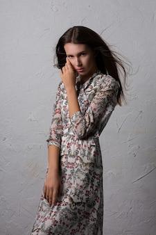 グラマラスな若い女性は灰色の壁に羽ばたき髪でポーズをとってファッショナブルなドレスを着ています
