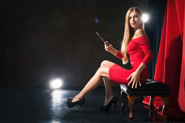 腰にステージの手でスツールに座っている赤いドレスを着たタバコを持つ魅力的な若い女性。