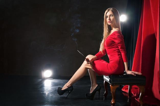 ステージ上の椅子に座って赤いドレスを着たタバコを持つ魅力的な若い女性。