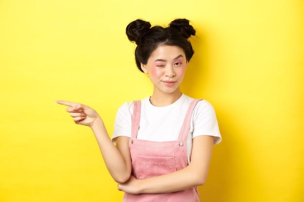 明るい化粧、左手の人差し指、カメラでウインク、黄色の上に立って、良いプロモーション取引のヒントを持つ魅力的なアジアの女の子。