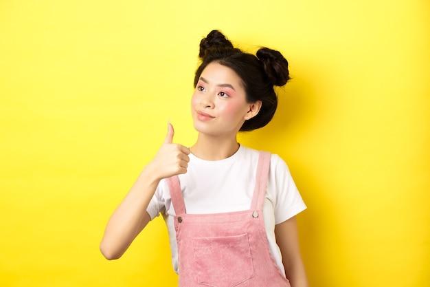 ピンクの化粧と夏服の魅力的なアジアの女の子、親指を上にしてロゴを左に見て、承認と賞賛、黄色の上に立っています。