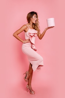 Glamour blonde girl with surprise face holding gift box and standing over rose wall in elegant pink dress. ecstatic emotions.
