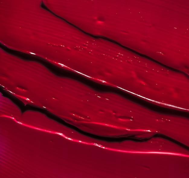 グラマーブランディングとメイクアップアートコンセプト赤い化粧品テクスチャ背景メイクアップとスキンケア化粧品製品クリーム口紅保湿剤マクロとして高級美容ブランドホリデーフラットレイデザイン