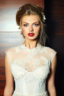 Glamour closeup portrait of beautiful blond bride with bright makeup and red lips