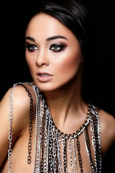 Glamour closeup portrait of beautiful young woman with juicy lips, bright black makeup and jewelry isolated on black