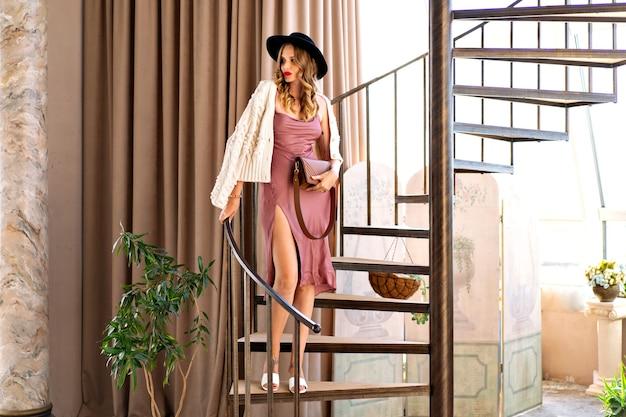 매력적인 우아한 금발 곱슬 행복한 금발 여성이 계단에서 포즈를 취하고 세련된 저녁 복장을 하고 화장을 합니다.