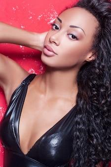 グラマーファッションモデル。赤い背景に対してポーズとメイクと髪型を持つ美しい若いアフリカ系アメリカ人女性