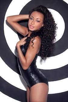 グラマーファッションモデル。剥ぎ取られた背景に対してポーズをとってメイクと髪型を持つ美しい若いアフリカ系アメリカ人女性