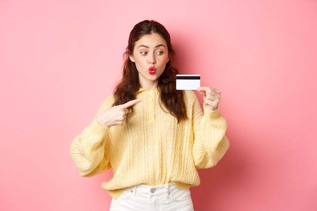 Glamour girl going shopping, looking excited and pointing at plastic credit card, standing against pink wall.