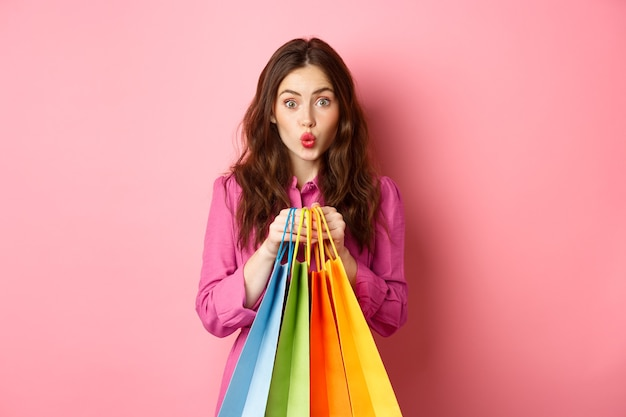 ピンクの壁に立って、買い物袋、パッカーの唇を持ち、恥ずかしそうに見える魅力的な女の子。
