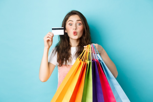 Glamour girl showing plastic credit card and shopping bags, pucker lips for kiss, standing happy against blue background. copy space