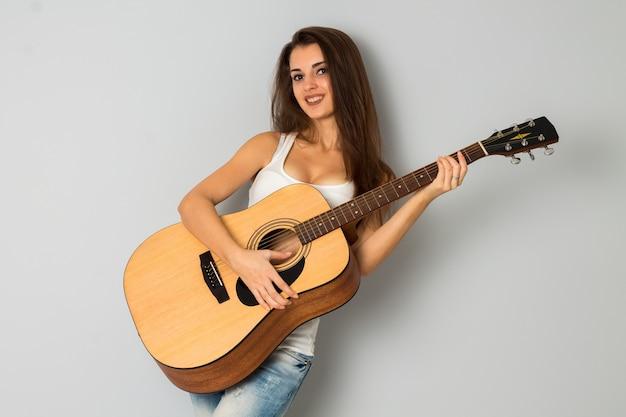 カメラを見て、灰色の背景のスタジオで笑っている手にギターを持つグラマーガール