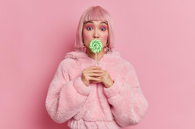 Glamour splendida signora asiatica con trucco luminoso copre la bocca con lecca-lecca verde rotondo indossa parrucca di capelli rosa e pelliccia posa al coperto. la ragazza di mllennial tiene caramelle al caramello sul bastone ha un debole per i dolci