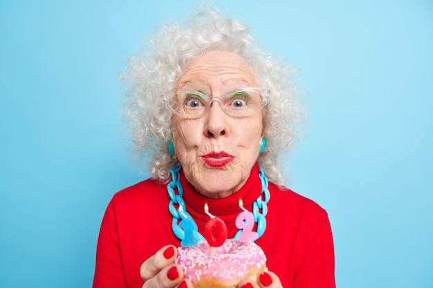 Гламурная бабушка в стильной одежде празднует день рождения в одиночестве, держит пончик со свечами, носит макияж, сохраняет губы округлыми более века.